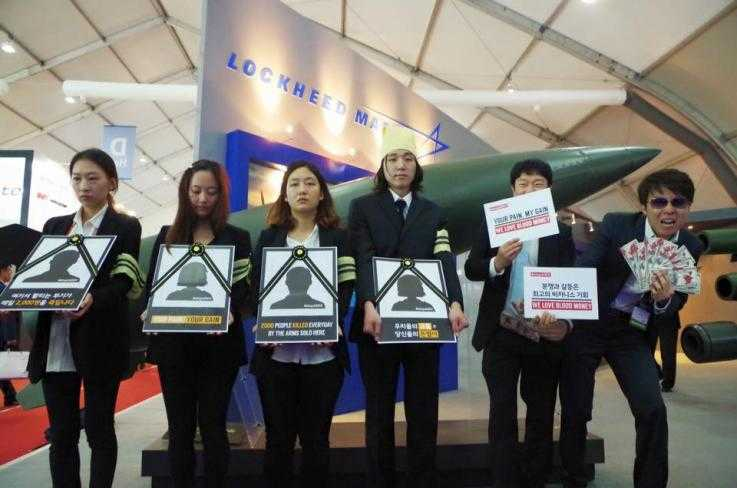 Activists stand in front of the Lockheed Martin exhibit at the ADEX arms fair