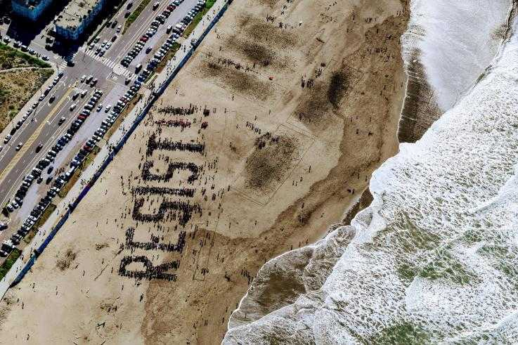"A large number of protesters spell out the words ""Resist"" on a beach"