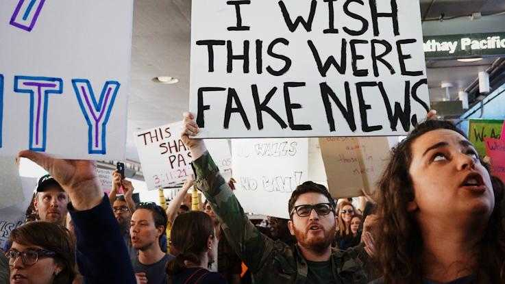 "A protester holds a placard reading ""I wish this were fake news"""