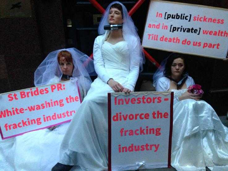 Three female protesters blockade the entrance of a PR company that supports the fracking industry