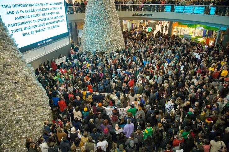 A huge group of protesters stand under an electronic sign in a shopping mall during a protest. The sign demands they disperse or face arrest.