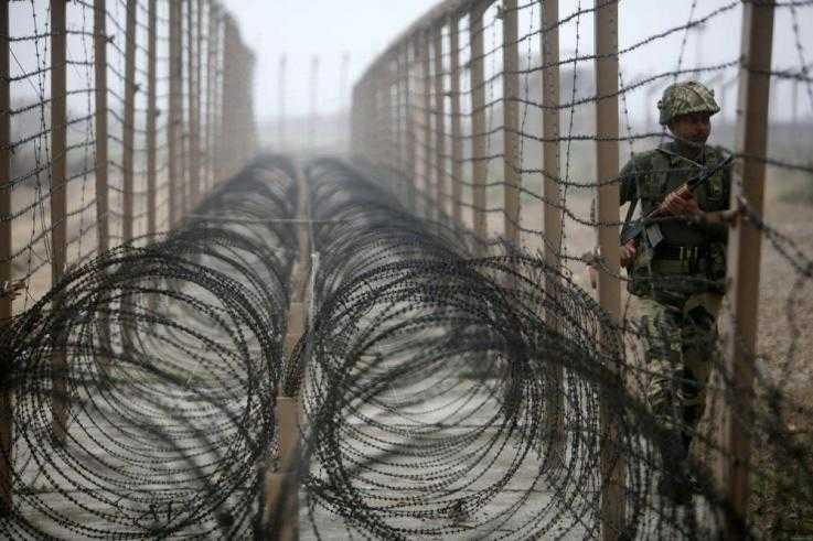 Coils of barbed wire lie between two fences with a soldier patrolling the other side of the right-hand fence