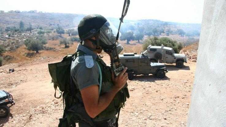 A member of Israel's Border Police wearing a gas mask. There are several armoured vehicles parked in the background.