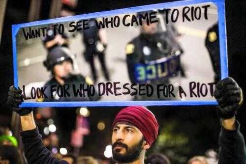 "A man holds a mirror to the police, on which is written ""Who came dressed for a riot?"""