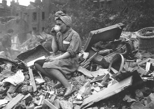 A woman drinks a cup of tea amid a destroyed building. The photo is black and white.