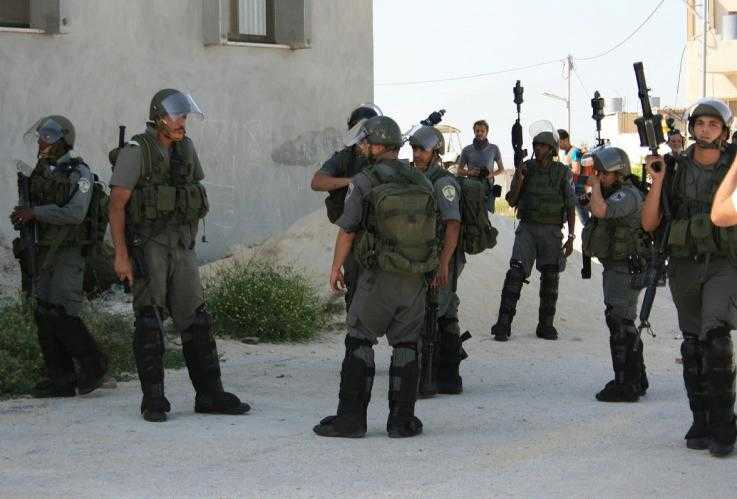 MAGAV border guards dressed in body armour and helmets stand at ease on a street corner.  Some have their guns down by their side and others have them pointing up in the air.