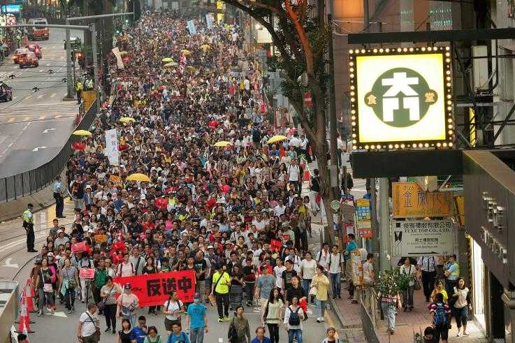 A large number of protesters march down a street