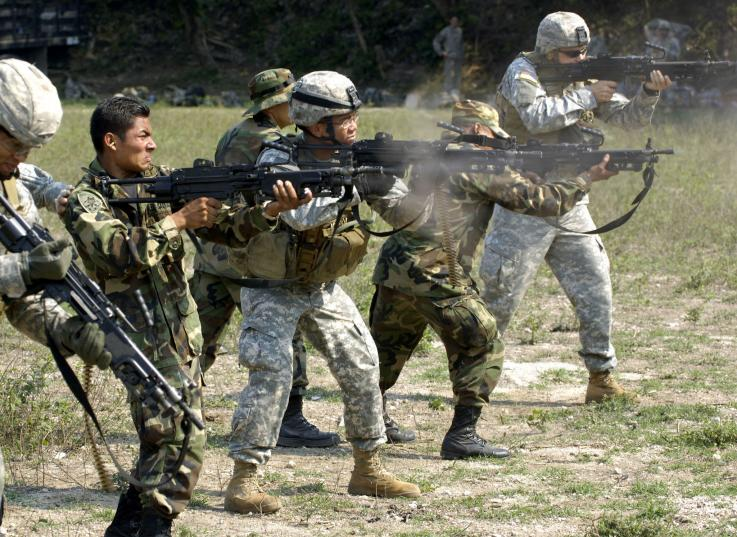 Soldiers from the USA and Mexico stand in a line, firing machine guns
