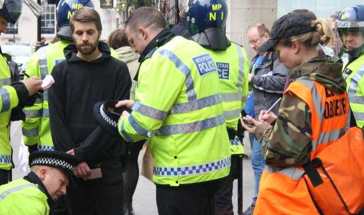A protester is detained by police as a legal observer looks on and takes notes
