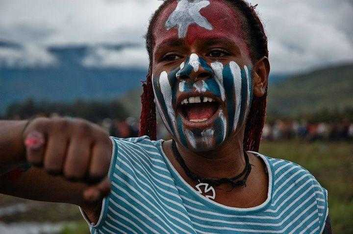 A young girl with the West Papuan flag at an independence rally