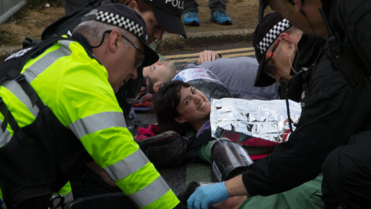 Police try to remove a protester from a lock-on blockade