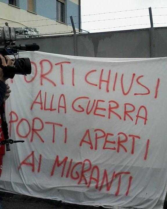 "A banner in Italian protests reading ""port closed to war, open to migrants"""