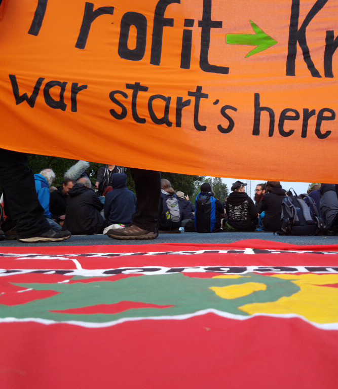 "Protesters sit below an orange banner reading ""war starts here"""