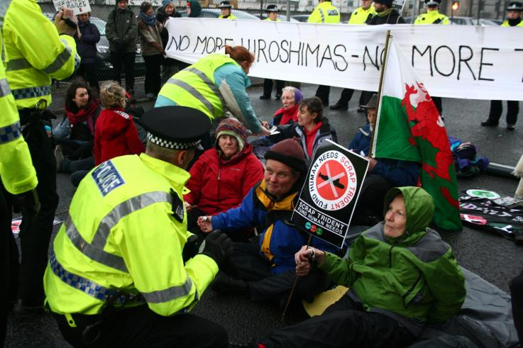 A group of people blockade a nuclear weapons factory in the UK. With their arms linked they talk to a police man.