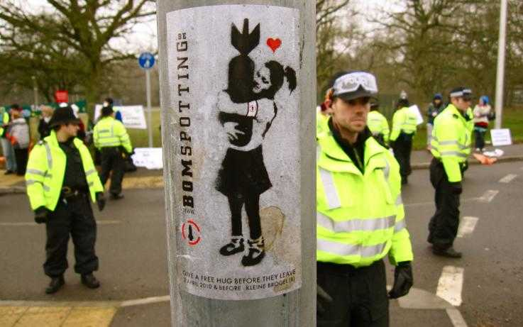 A picture of a sticker on a lamppost, of a girl hugging a nuclear bomb, with police in the background