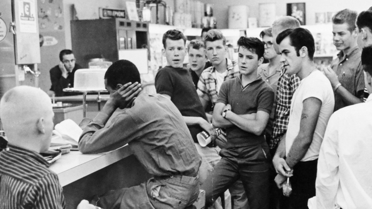 A large group of white young men taunt a black protester during the US civil rights movement.