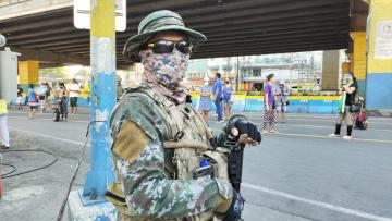 A soldier stands in a street with a gun, wearing a face mask.