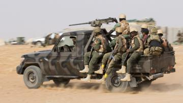 A group of soldiers on a large jeep driving through the desert. The jeep has a large gun on top and the soldiers are armed.