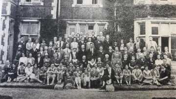 A black and white photo showing many people sat outside in front of an old building