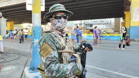 A soldier stood in the street wearing a face mask