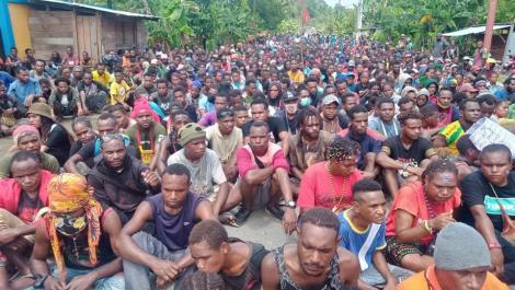 A large crowd of Papuans sit on the ground.