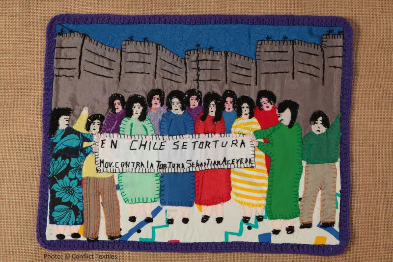 En Chile se tortura / Demonstration against torture, Chilean arpillera, Violeta Morales, 1988, Photo Martin Melaugh, Oshima Hakko Museum collection, Japan. In the care of Conflict Textiles collection