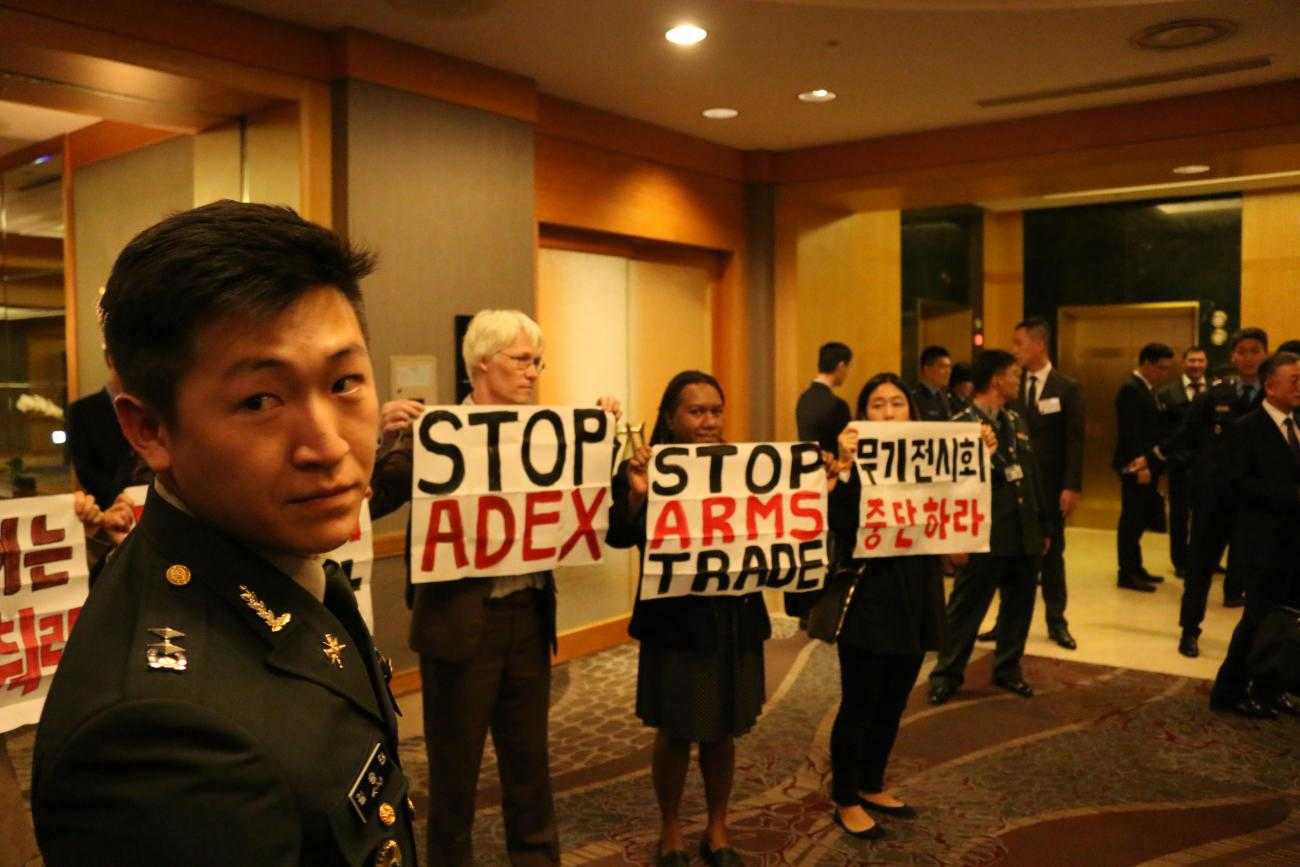 International activists inside the arms dealers welcome dinner at ADEX 2015 in Seoul. Protesters hold up banners saying 'Stop ADEX' whilst a soldier looks on