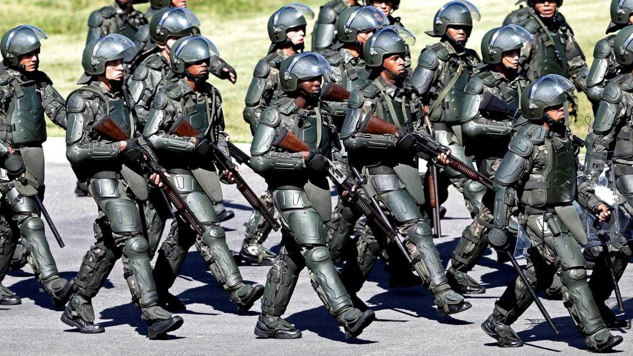 A large number of heavily armoured police, with guns, march in Brazil