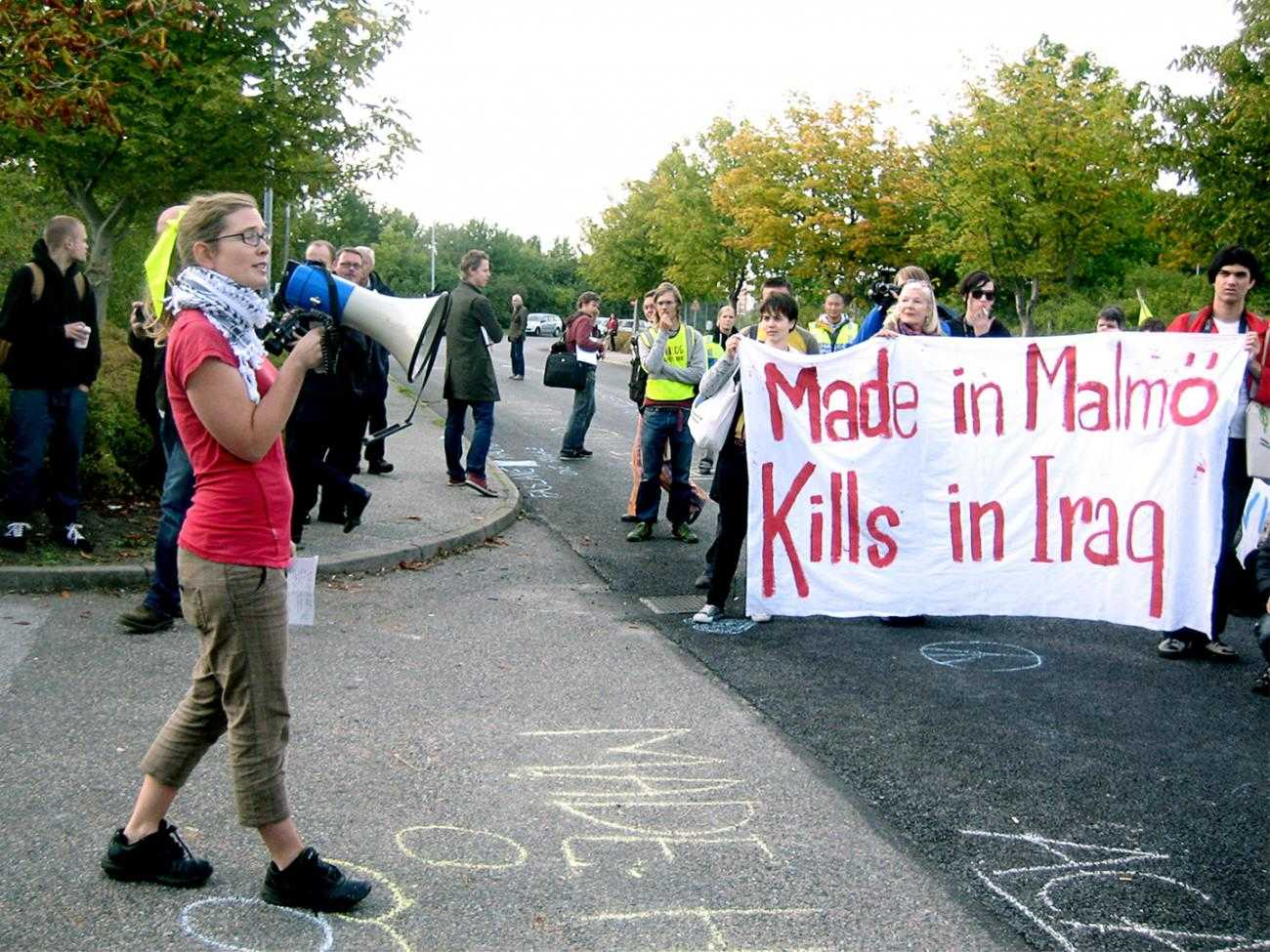 "A protest out side Aimpoint's factory. A banner reads ""Made in Malmo, Kills in Iraq"""