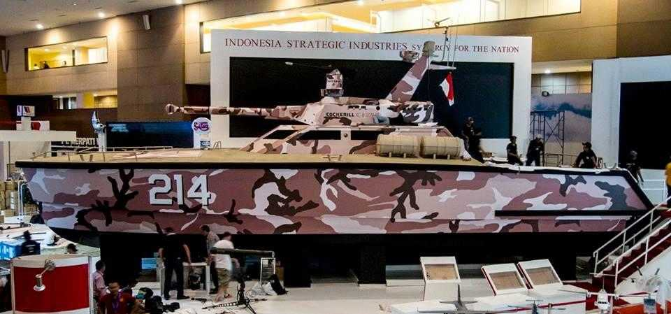 "CMI Defences ""tank boat"" - a catamaran with a large turret, exhibited indoors at a trade show. The boat is painted in brown camoflage patterns."
