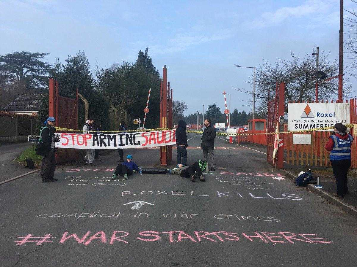 "Activists hold a ""stop arming saudi"" banner across a gate that is blocked by people in a lock-on tube. The floor has been chalked with the words ""War Starts Here"""