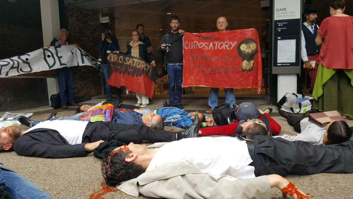 "A large group of people lie on the floor as part of a ""die-in"". In the background other protesters stand with banners."