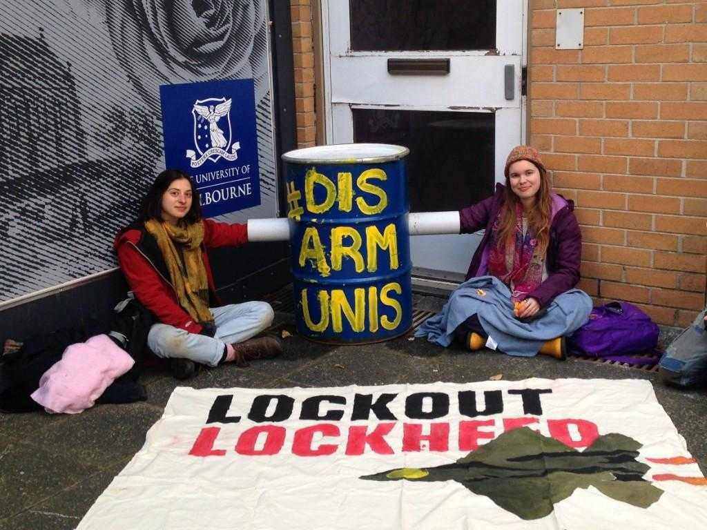 "Two student activists lock on to a barrel filled with concrete. The barrel is painted blue and has the words ""Disarm Unis"" painted on it. In front of the activists there is a banner reading ""Lockout Lockheed"". Behind them is a sign for the University of Melbourne"
