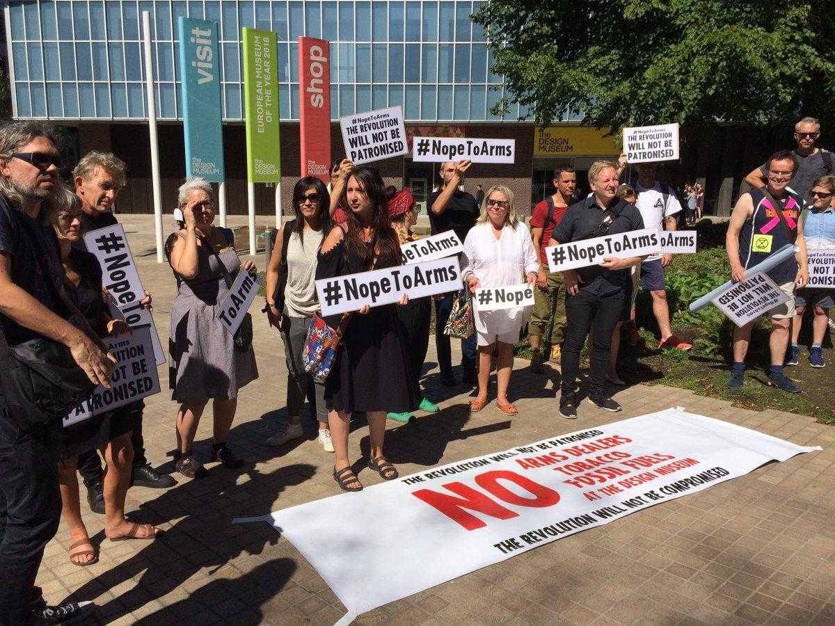 "A large group of activists stand with placards reading ""Nope To Arms"" outside the Design Museum in London"