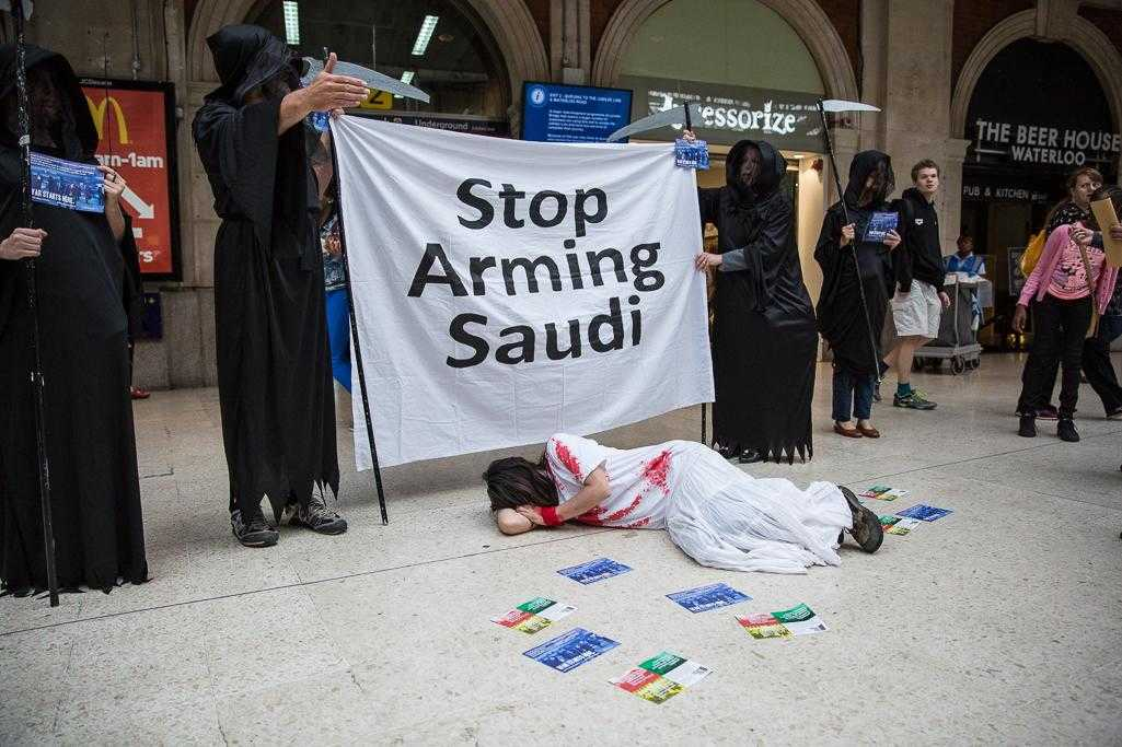 "Activists dress in black ""grim reaper"" outfits and hold a banner reading ""Stop Arming Saudi"""