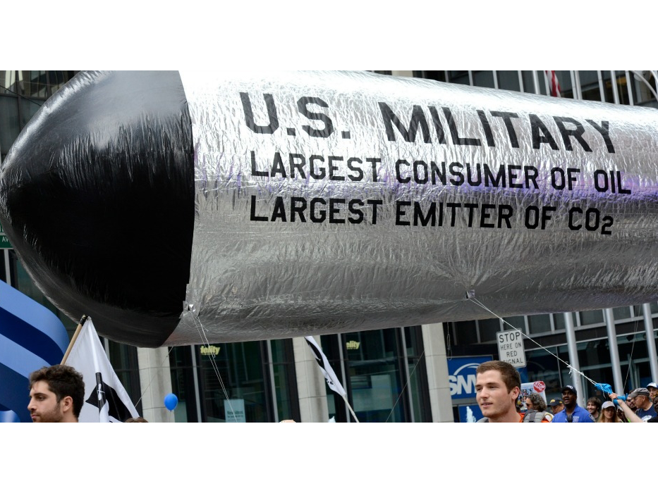 "A number of people walk with a large inflatable missile reading ""US military: largest user of oil and largest emitter of Co2"""