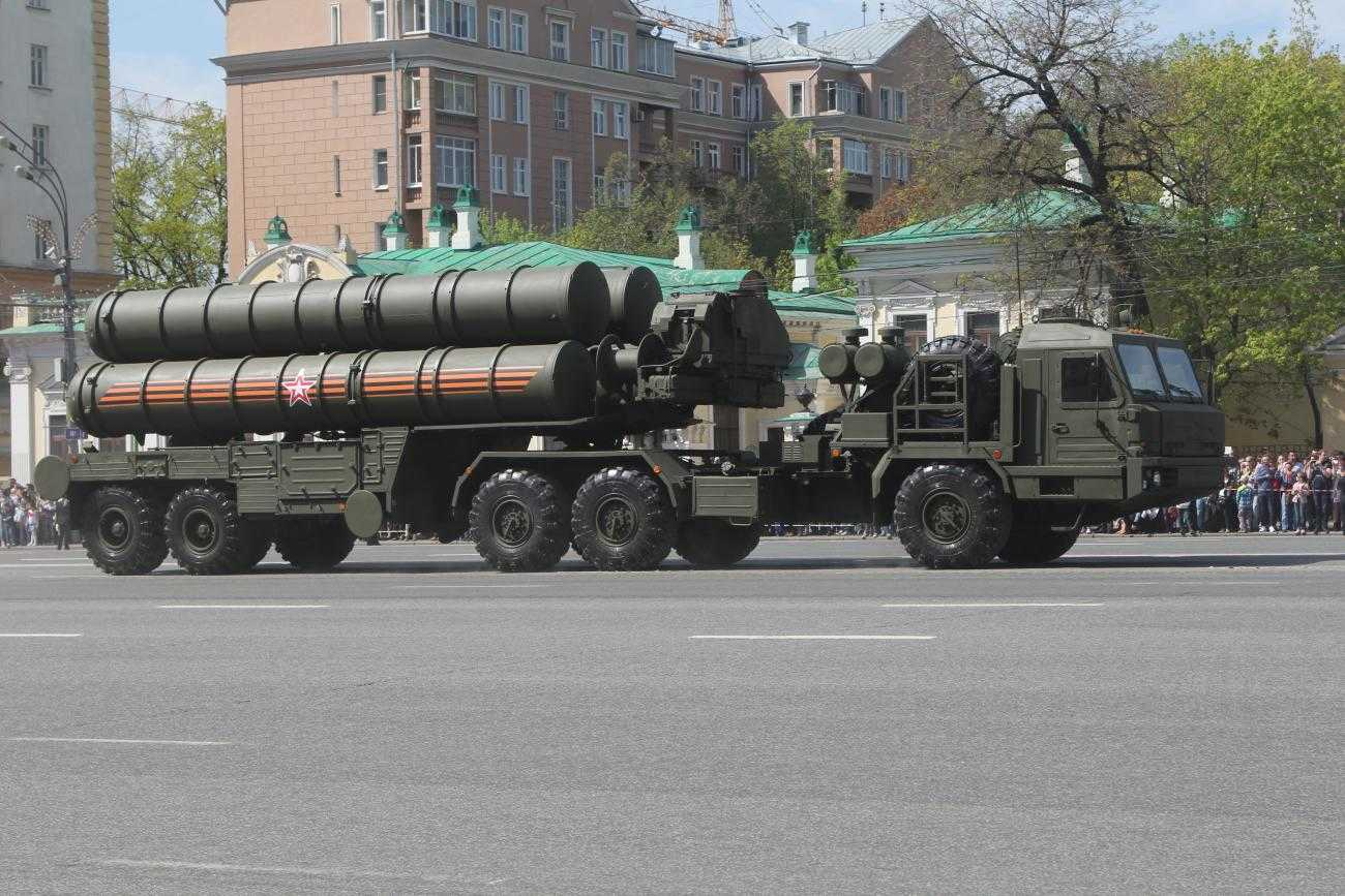 A large truck pulls an even larger trailer. On the trailer are several large missile launchers. Everything is painted dark khaki green