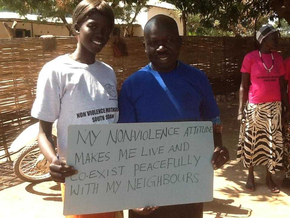 "Activists hold a sign saying ""My nonviolence attitude makes me live peacefully and coexist with me neighbours"""