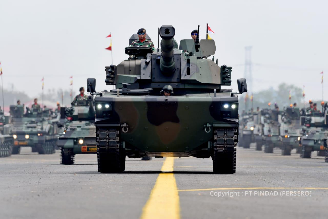 A tank being used in a military display. In the background are many other military vehicles