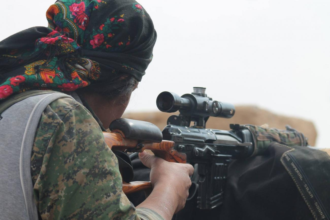 A woman with her back to the camera aims down a rifle