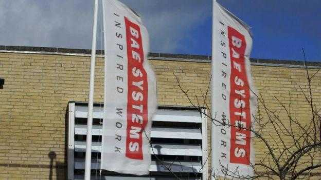 A BAE Systems office. Two flags with the BAE Systems logo fly outside.