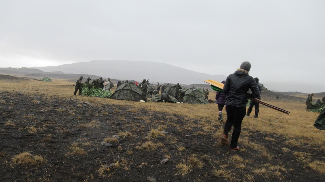 Members of CAM go to speak to NATO soldiers putting up tents during Trident Juncture