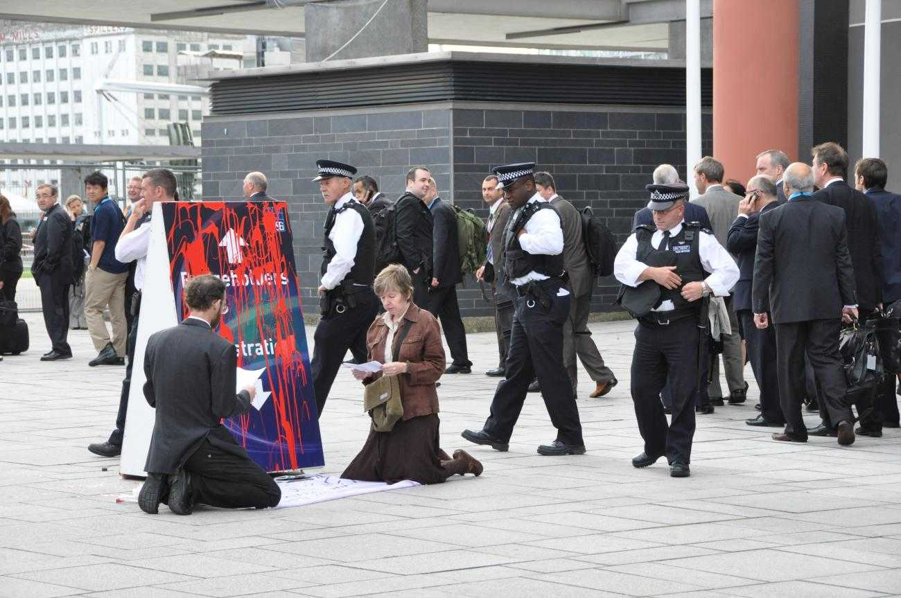 Two activists kneel in front of a sign directing people to DSEI, which has been covered in red paint, to symbolise spilt blood. Behind them a queue of people wait to go into the fair. Three police officers are approaching the activists.