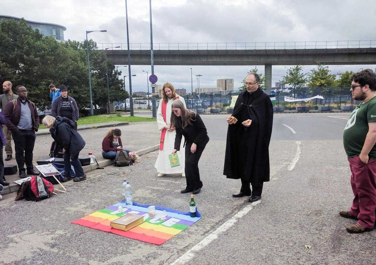 A group of prieces give communion at the DSEI protests