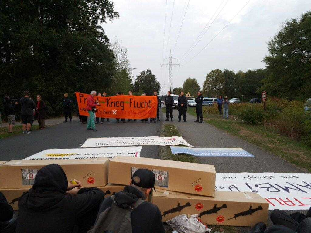 "Activists sit behind a blockade of ""delivery boxes"" across the road. In the distance there is an orange banner reading ""war starts here, let's stop it here!"""