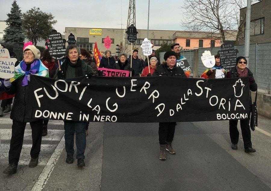 Four women from Women in Black Bologna hold a banner on a protest against the RWM factory in Ghedi