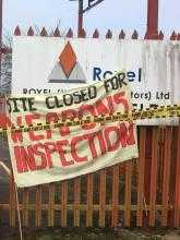 "A banner reading ""Site closed for weapons inspection"" stands in front of the entrance sign of an arms company called Roxel."