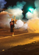 A man stands with his back to the camera and fist raised amidst clouds of tear gas