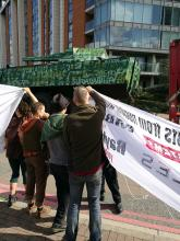 Activists hold banners as a tank drives past in the background