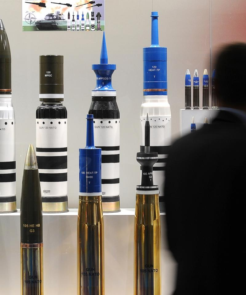 A man looks at a large range of missiles at the DSEI arms fair.